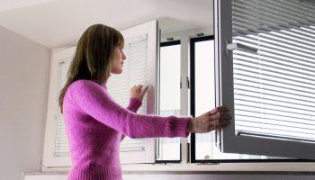 Frau öffnet ein Fenster